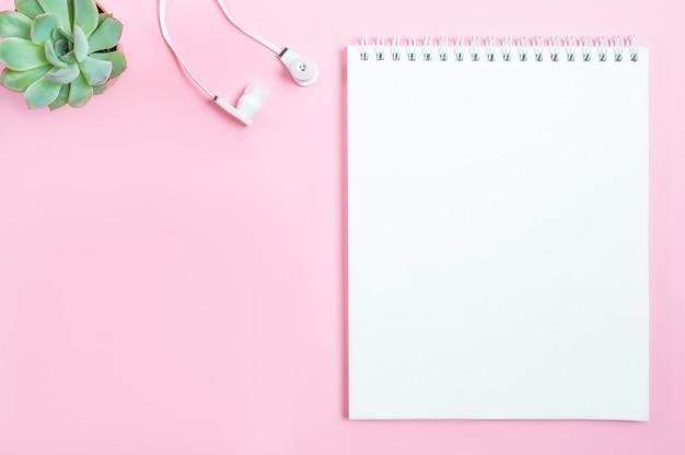 Espaço de trabalho: o bloco de notas, fones de ouvido e flor suculenta no fundo rosa