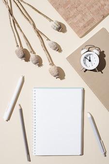 Espaço de trabalho outono com caderno aberto com páginas em branco e relógio branco