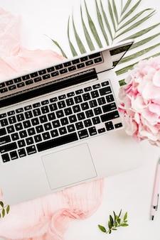 Espaço de trabalho para mulher em uma mesa de escritório em casa com laptop, buquê de flores de hortênsia rosa, cobertor pastel, placa de folha monstera e acessórios na superfície branca