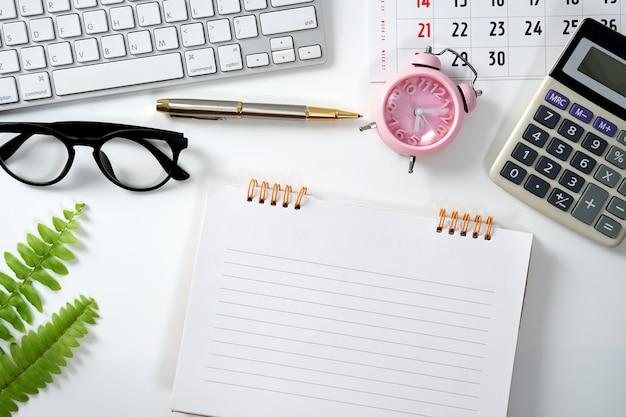 Espaço de trabalho para trabalhar mesa branca de madeira com óculos e suprimentos de calendário de calculadora de teclado