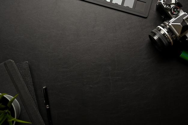 Espaço de trabalho plano criativo com material de papelaria para câmera e espaço de cópia na vista superior da mesa preta