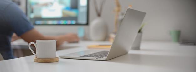 Espaço de trabalho portátil com laptop aberto, xícara de café e suprimentos na mesa de escritório branco na sala de escritório