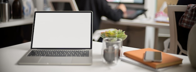 Espaço de trabalho portátil com laptop, caneca de café, smartphone e notebooks