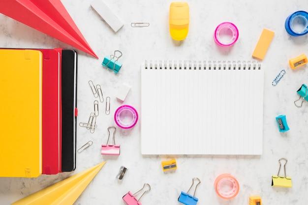Espaço de trabalho que consiste em um caderno em branco e material de escritório em torno dele