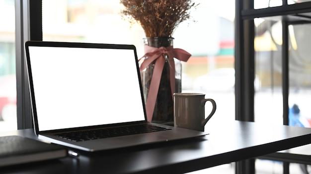Espaço de trabalho quente perto da janela com computador laptop de tela em branco, xícara de café, caderno e planta na mesa.