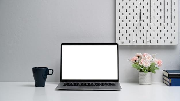 Espaço de trabalho simples com mesa branca para laptop