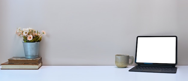Espaço de trabalho simples com tablet de computador de tela em branco, caderno, xícara de café e vaso na mesa branca.