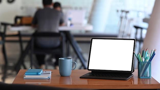 Espaço de trabalho simples com um computador tablet, artigos de papelaria, caderno e xícara de café na mesa de madeira.
