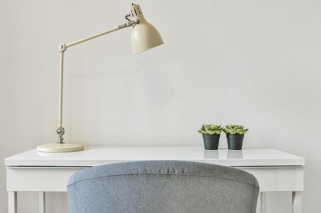Espaço de trabalho simples em uma casa moderna. vista de uma mesa elegante com abajur e plantas
