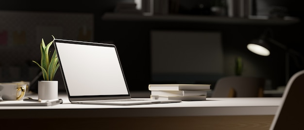 Espaço de trabalho tarde da noite laptop aberto sob a luz no escuro decoração do quarto com material de escritório
