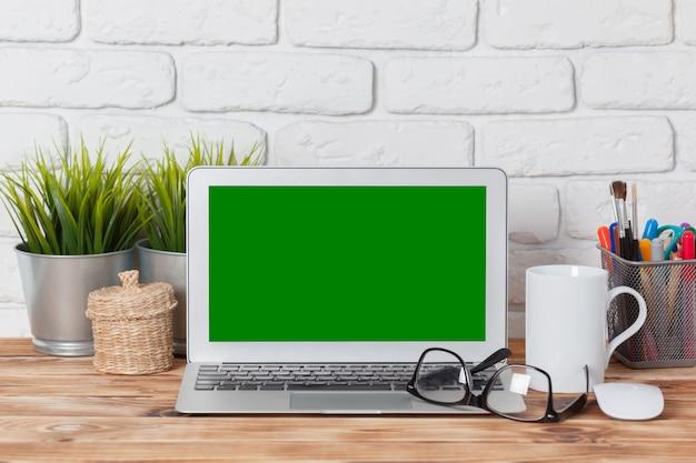Espaço de trabalho, tela em branco do laptop na mesa de madeira,