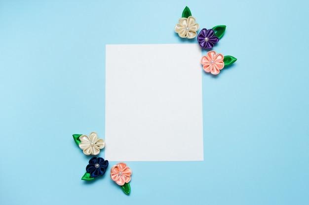 Espaço em branco de papel com flores de cetim e espaço de cópia sobre um fundo azul.