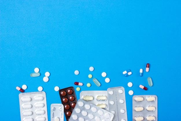 Espaço em branco para o texto. comprimidos, cápsulas. fundo de papel azul. vista do topo.