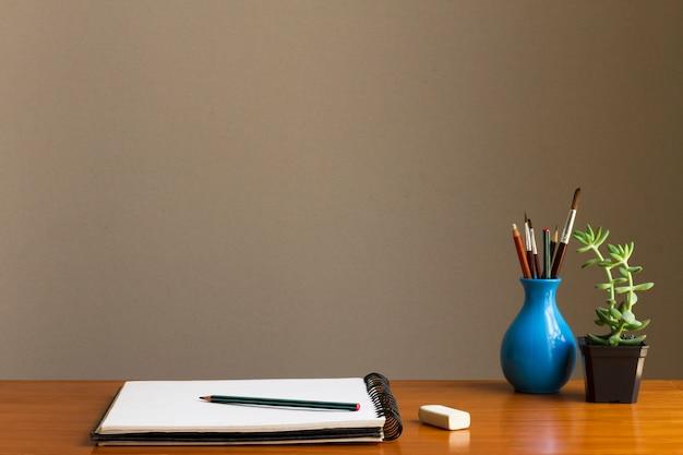 Espaço mínimo de trabalho de artista com pincéis de desenho e arte