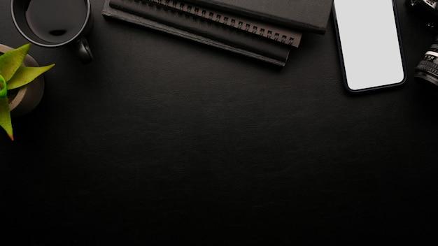 Espaço para exibição com maquete de smartphone notebook preto planta de café fundo preto vista superior