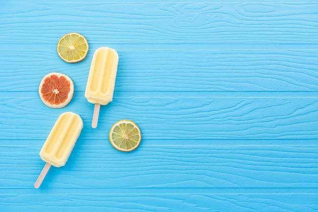 Espaço sorvete palito de limão sobre fundo azul pastel