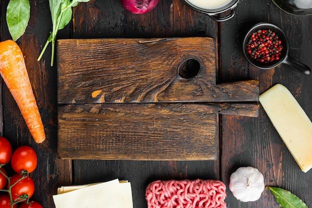 Espaço vazio, conjunto de tábua de corte limpo o conceito de cozinhar lasanha ingredientes italianos folhas de lasanha carne ervas tomate molho bechamel na velha mesa de madeira escura