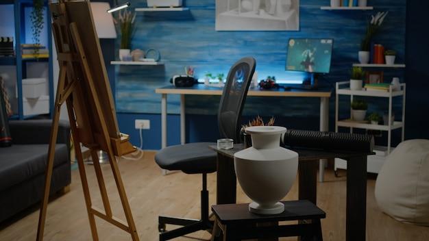 Espaço vazio de estúdio de arte com cavalete e tela branca