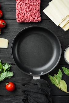 Espaço vazio limpo conjunto de panela de ferro fundido o conceito de cozinhar lasanha ingredientes italianos folhas de lasanha carne ervas tomate molho bechamel na vista de mesa de madeira preta