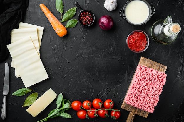 Espaço vazio limpo conjunto de quadros o conceito de cozinhar lasanha ingredientes italianos folhas de lasanha carne ervas tomates molho bechamel na vista de cima da mesa de pedra preta
