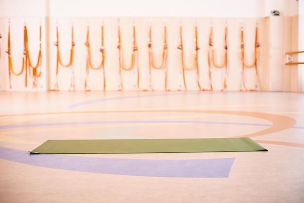 Espaço vazio no centro de fitness, parede de tijolos, piso de madeira natural, estúdio moderno, tapete de ioga desenrolado no chão.