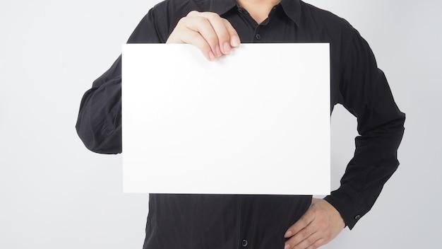 Espaço vazio para o texto. mão e camisa preta do desgaste de asiáticos masculinos está segurando a placa de papel em branco sobre fundo branco.