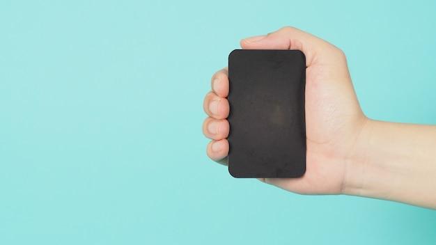 Espaço vazio para o texto. mão masculina segurando o cartão preto em branco isolado em fundo verde menta ou azul tiffany.