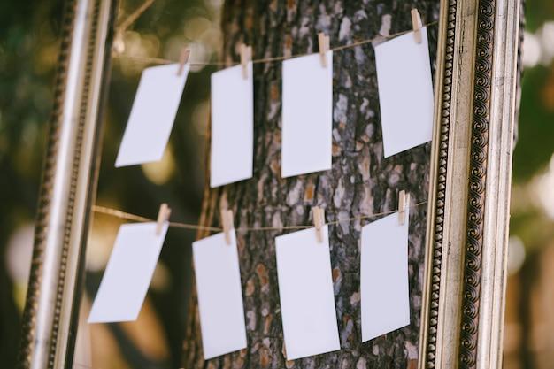 Espaços em branco para a lista de convidados do casamento pendurados em uma bela moldura em uma planta de assentos de árvore de perto