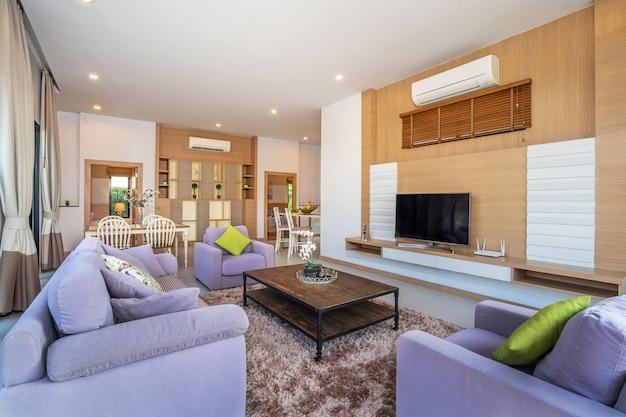 Espaçosa sala de estar com vista para a piscina e sofá roxo