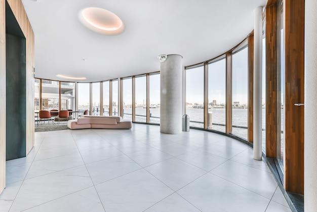 Espaçosa sala de plano aberto com área de estar e coluna contra fileira de janelas panorâmicas com vista para o canal da cidade