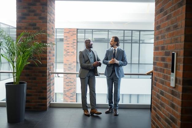 Espaçoso centro de negócios. dois empresários em um amplo centro comercial pela manhã tomando café