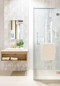 Espaçoso e moderno interior de casa de banho com cabine de duche com parede de vidro e pia de torneira