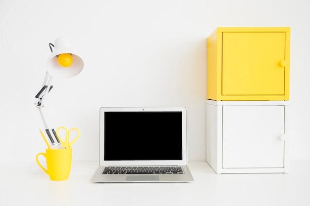 Espaçoso local de trabalho em cores brancas e amarelas com caixas de metal
