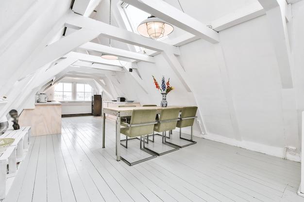 Espaçoso quarto no sótão do apartamento com mesa de jantar e cadeiras perto da cozinha aberta sob o telhado com vigas