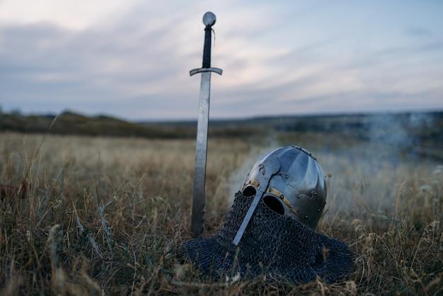 Espada cravada no chão e capacete de cavaleiro de metal, ninguém, símbolo de grandes guerreiros em campo