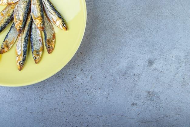 Espadilha salgada pequena e batatas fritas em um prato, no fundo de mármore.