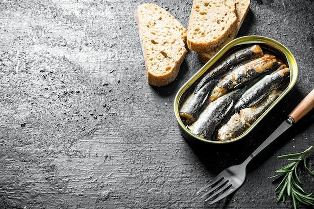 Espadilhas em uma lata com pão fatiado na mesa de madeira preta
