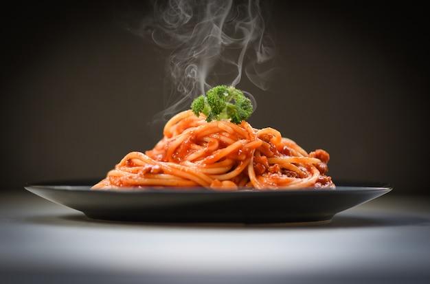 Espaguete à bolonhesa em fundo preto / macarrão italiano espaguete servido na chapa preta com molho de tomate e salsa no restaurante comida italiana e menu
