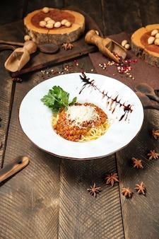 Espaguete à bolonhesa guarnecido com molho e salsa na mesa de madeira