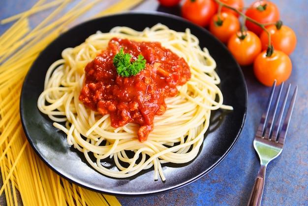 Espaguete à bolonhesa / macarrão italiano de espaguete servido na chapa preta com tomate e salsa no restaurante comida italiana e menu
