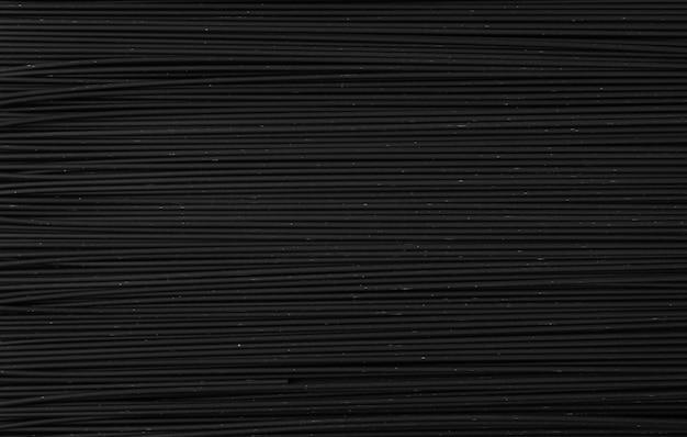 Espaguete caseiro preto cru em fundo escuro. textura de macarrão preto seco