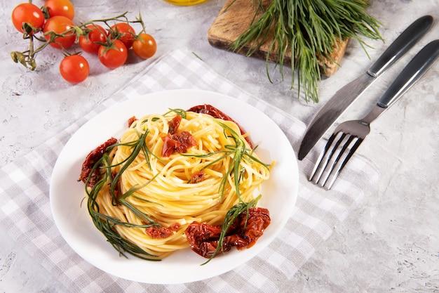 Espaguete com agretti, um vegetal da primavera da itália e tomate seco