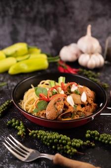 Espaguete com amêijoas em uma placa preta com pimentões alho e pimenta frescos.