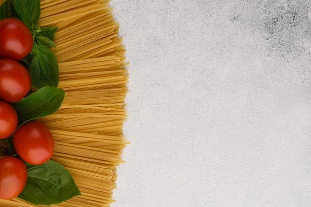 Espaguete com borda de tomate e manjericão. os tomates cereja com manjericão estão acima dos espaguetes no fundo de pedra com espaço da cópia.