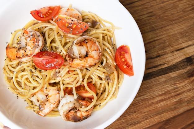 Espaguete com camarão frito e tomate fresco.