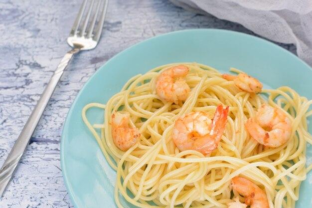 Espaguete com camarões em placas azuis. um jantar delicioso.