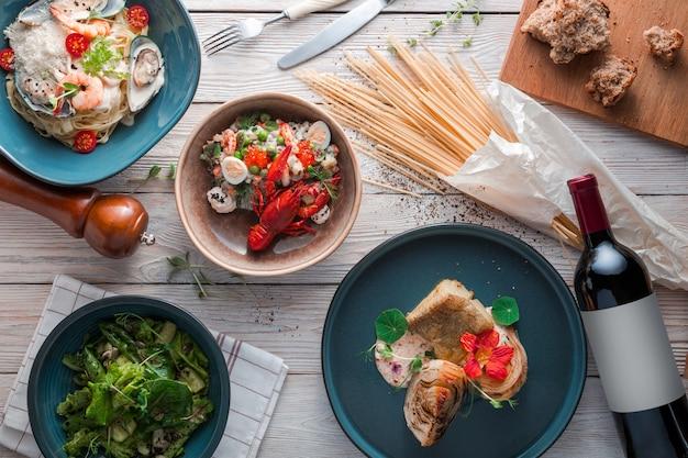 Espaguete com camarões no prato de cerâmico verde e servido com copo de vinho branco. vista superior, plana leigos.