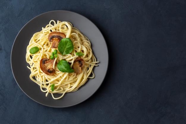 Espaguete com cogumelos e molho cremoso de alho em um espaço escuro