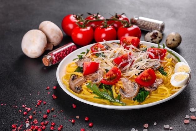 Espaguete com cogumelos, queijo, espinafre, rukkola e tomate cereja. prato italiano, cultura mediterrânea