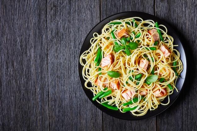 Espaguete com feijão verde e pedaços de salmão assado, decorado com folhas frescas de manjericão, servido em um prato preto sobre uma mesa de madeira escura, vista de cima, postura plana, cópia espaço